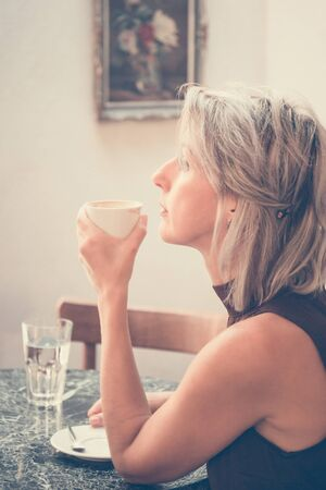 Toned picture of side view of beautiful blonde lady sitting in cafe or restaurant near window and drinking coffee