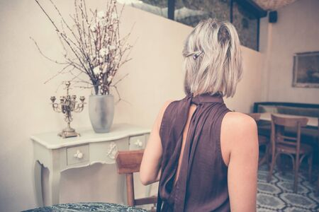 Toned picture of back view of beautiful blonde lady sitting in cafe or restaurant