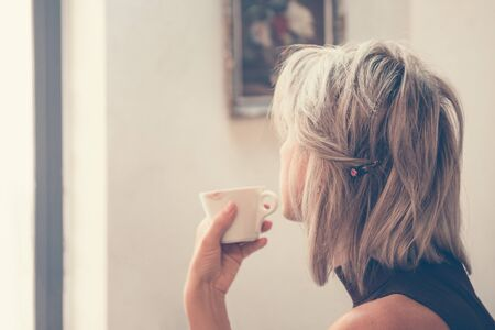 Toned picture of back view of beautiful blonde lady sitting in cafe or restaurant near window and drinking coffee
