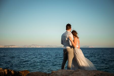 happy romantic wedding couple in love, men and women in white wedding dress on the beach and look at the horizon Imagens