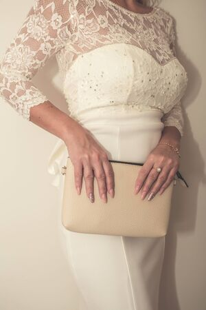 bride in a wedding dress holds in hand a white bag. Beautiful manicure. Wedding day. Wedding rings. Stock Photo