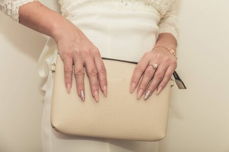 The bride in a wedding dress holds in hand a white bag. Beautiful manicure. Wedding day. Wedding rings.