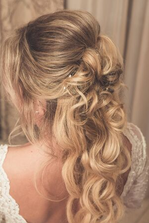 Hair stylist makes the bride before wedding Imagens