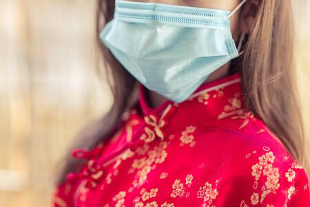 Children in traditional chinese dress in medicine mask. Coronavirus. Kid girl imprison at home for protection corona virus. coronavirus and epidemic virus symptoms.