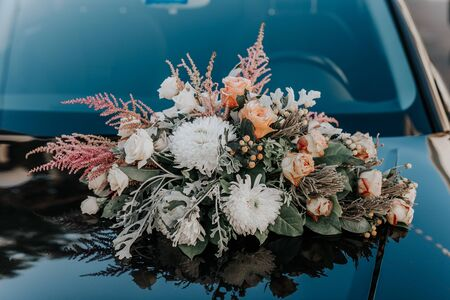 Fresh flowers on the car. Beautiful bouquet of flowers.Wedding bouquet in the background of the machine.