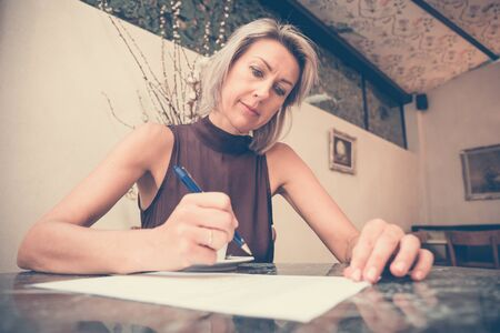 Toned picture of beautiful blonde lady sitting in cafe or restaurant near window and signs documents Stock Photo
