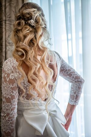 Beautiful bride in white wedding dress standing in her bedroom and looking in window