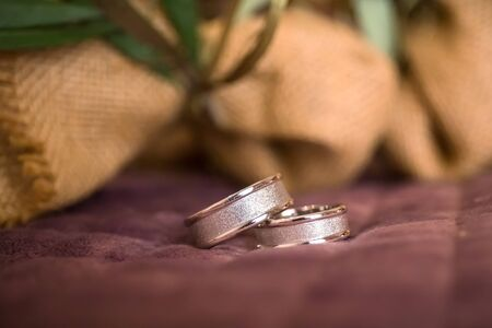 Beautiful toned picture with wedding rings lie on a surface against the background