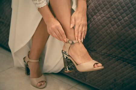 The Bride puts on wedding shoes on her tender feet Stock Photo