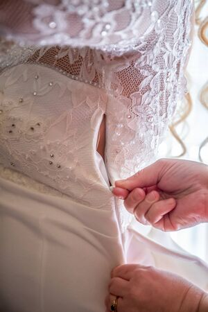 The wedding dress , buttons fastens the brides mother. rear view