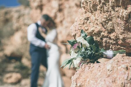 wedding bouquet of green and white flowers on the stone with bride and groom in background Stock Photo