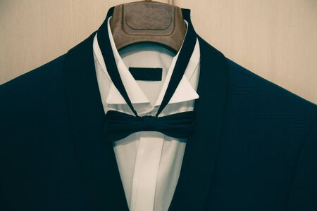 The stylish black suit with white shirt and bow tie on hanger . morning preparations before wedding day. groom outfit