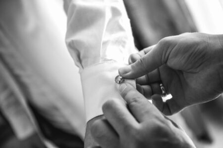 helps groom to put on cufflinks close up Stock Photo