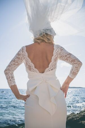 Beautiful bride in luxury wedding dress at the sea side. Wedding by the sea. Bride walking around the sea near the place of the wedding ceremony. Back view Stock Photo