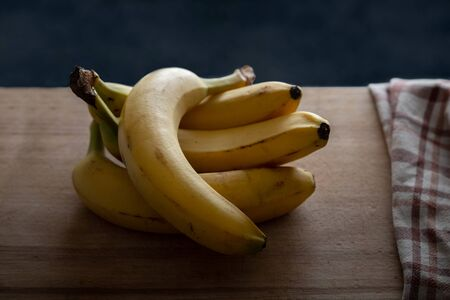 several fresh bananas lauing on wooden cutting board