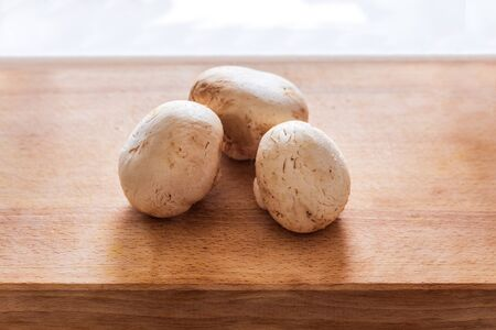 several fresh champignons laying on wooden cutting board Stock Photo