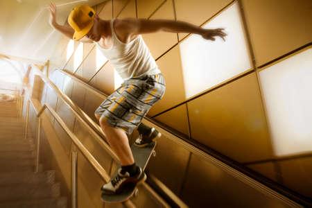 bajando escaleras: skater joven con capacete y pantalones cortos deslizándose por las escaleras delante de fondo amarillo y la iluminación posterior Foto de archivo