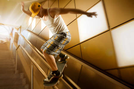 bajando escaleras: young skateboarder with basecap and shorts sliding down stairs in front of yellow background and back lighting Foto de archivo