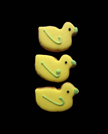 Three yellow duck-shaped biscuits isolated on a black background. photo
