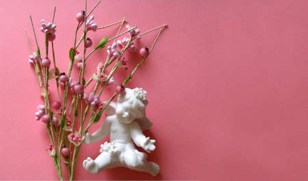 A baby angel on a pink background with flowers on his side. photo