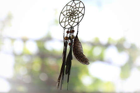A dreamcatcher against a blurred background of leaves.