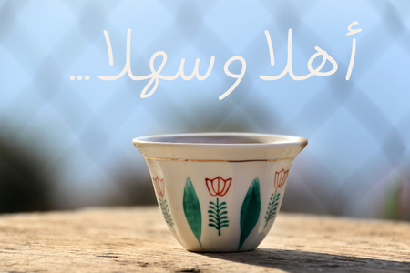 A traditional Lebanese coffee cup on a wooden table with the tradition Lebanese greeting to make guests welcome.