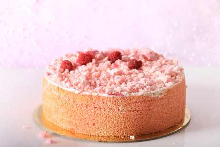 A pink cake covered with meringue crumbles, raspberries, and sugary rose petals.