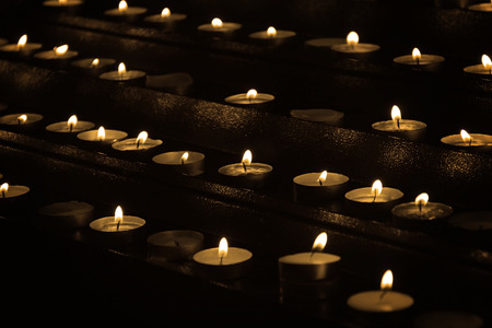 Many candles lit inside a Catholic church.