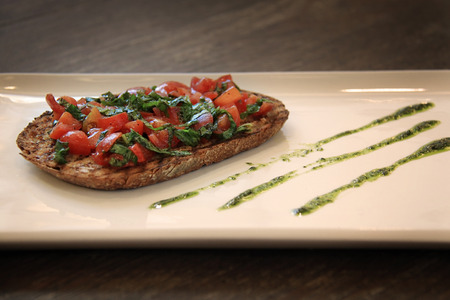 Bruschetta toast with tomatoes and pesto on a plate.