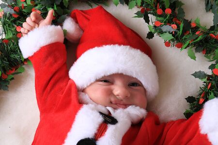 A grumpy newborn baby in a Santa Claus outfit, the Christmas Grinch.