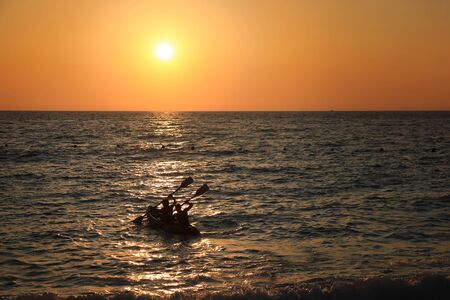 Two men rowing their boat in the Mediterranean sea during sunset.