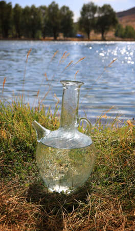 A traditional Lebanese water jug near a water pond.