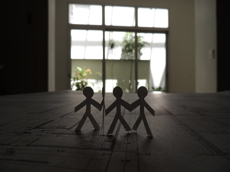 split level: silhouette of four people on cutted paper over a project plan