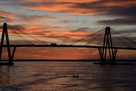 corrientes: men at a distance on lonely boat under bridge Manuel Belgrano on Parana river, Corrientes, Argentina