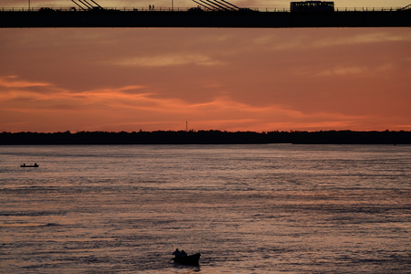 chaco: men at a distance on lonely boat under bridge Manuel Belgrano on Parana river, Corrientes, Argentina