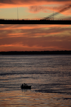 men at a distance on lonely boat under bridge Manuel Belgrano on Parana river, Corrientes, Argentina