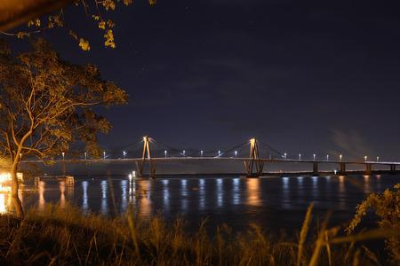 corrientes: night cityscape of Manual Belgrano Bridge on Parana river, Corrientes, Argentina