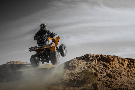 Man on quad in adventure at desert as extrem sport Foto de archivo