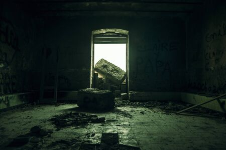 Light of hope entering from a failed door in a ruined abandoned place in zombie survival mode