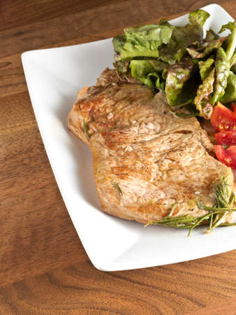 side of beef: A piece of beef steak on a white plate with lettuce and tomatoes on the side on a wood background