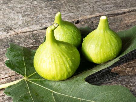 fig leaf: Three fresh figs on a fig leaf on a wooden surface
