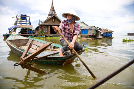 boat house: Kompong luong, Cambodia - 2010, August 13 : A Cambodian woman in a boat in the floating village of Kompong Luong on the Tonle Sap lake in Cambodia Editorial