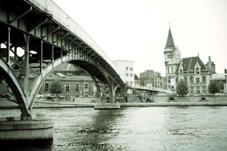oficina antigua: La pasarela Saucy sobre el r�o Mosa y la antigua oficina de correos, en la ciudad belga de Lieja en la regi�n de Valonia de B�lgica
