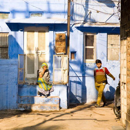 rajasthani: Jodhpur, India - 2015, January 3 : An old rajasthani woman sitting on a porch and a kid in school uniform walking at dawn on the street in the old blue city of Jodphur, Rajasthan, India Editorial