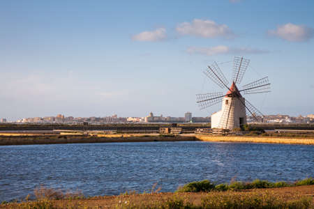 western part: A windmill in a salt pan withTrapani in the background in the western part of Sicily in Italy