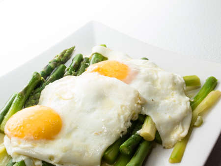 A plate with two fried eggs on a bed of asparagus vegetables Stock Photo