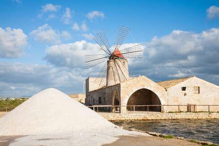salina: A salt pan windmill and heap of sea salt near Trapani in western Sicily, italy Stock Photo