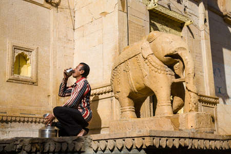 ki: Jaisalmer, India - 2015, January 7 : The guard of the Salim Singh Ki Haveli in the historic center of Jaisalmer drinking from a cup next to the entrance with an elephant sculpture
