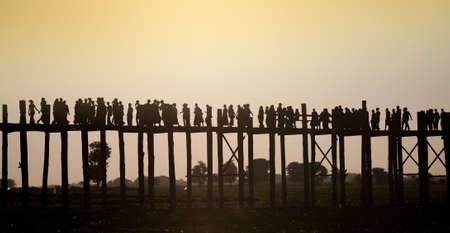 People walking at sunset on the U Bein teakwood bridge in Amarapura near Mandaly in central Burma