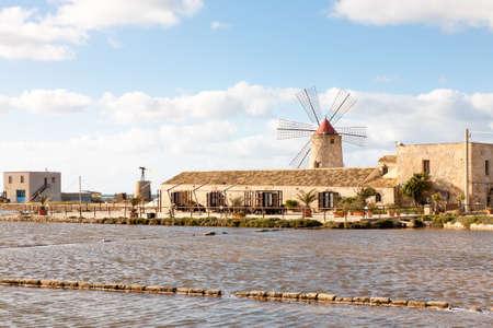 salina: A salt pan or salina in the Nubia area near Trapani with traditional windmill Stock Photo